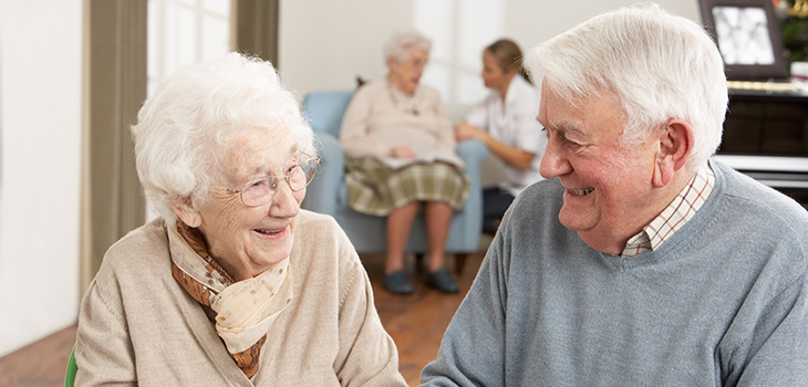 elderly couple smiling fondly at each other in the recreation room in from of a piano