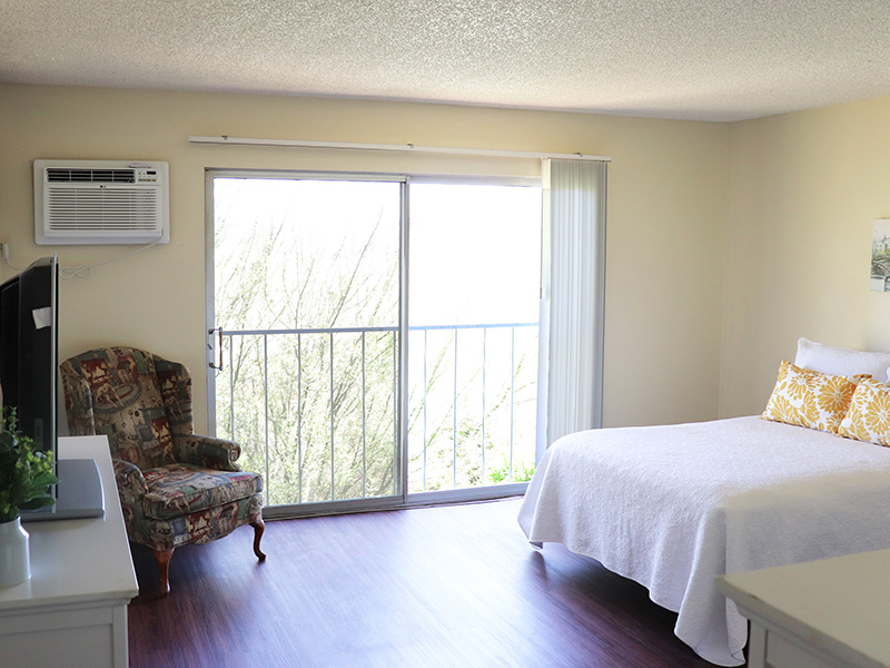 Resident bedroom with clean wood floors and a sliding glass door letting in natural light.