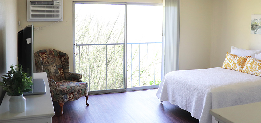 Bedroom with large sliding door letting in natural light. Clean hardwood floors and spacious room.