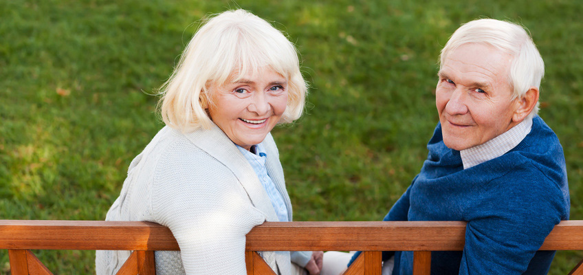 elderly couple holding hands sitting on a bench outside