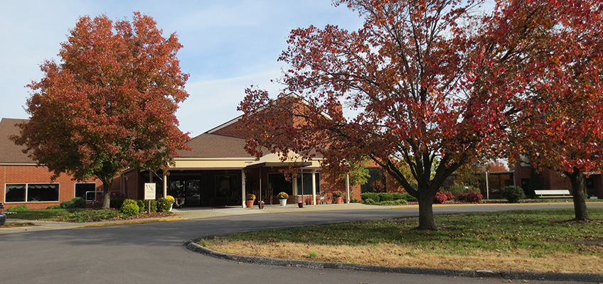 Exterior view of building with mature trees and circular driveway