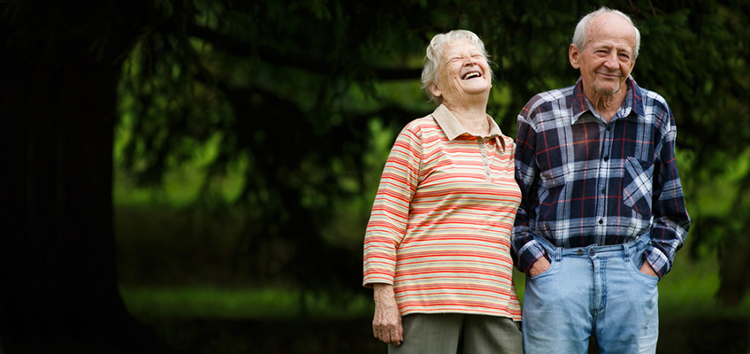 elderly couple walking outside while laughing and smiling