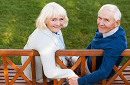 elderly smiling couple holding hands on a bench outside