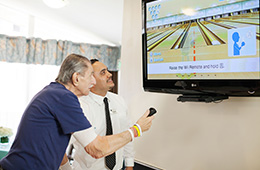 resident and staff member playing wii bowling