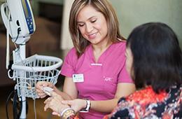 woman nurse helping a woman take blood pressure
