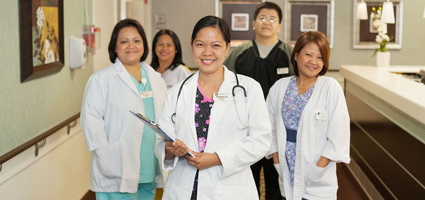 Staff picture with 5 members wearing doctors coats and a stethoscope and a clipboard