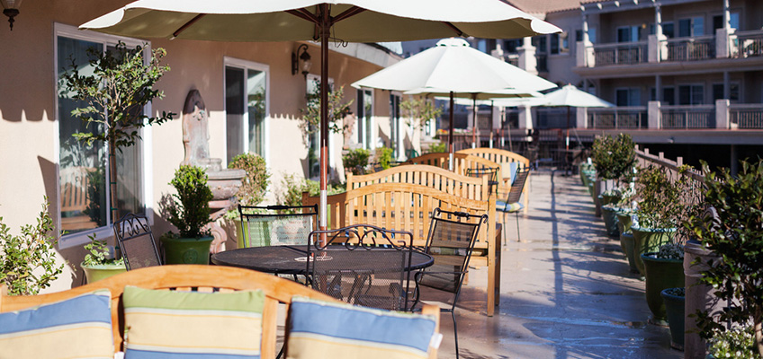 outside tables and chairs with umbrellas with a resort feel
