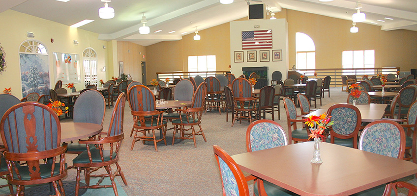 Resident dining area with flowers set on each table and an american flag hanging on the wall
