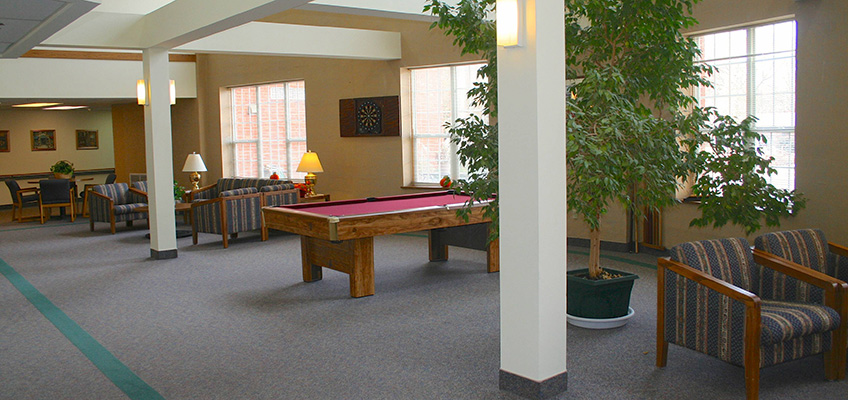 Activity room with a pool table and various areas to sit in for activities
