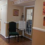 The beauty shop entrance with a chair out side of the double doors and a sign with services