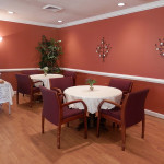 Dining area for residents with nice table cloths on the table and flowers in vases