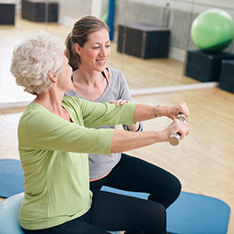 A senior performing exercises with another female in a gym.