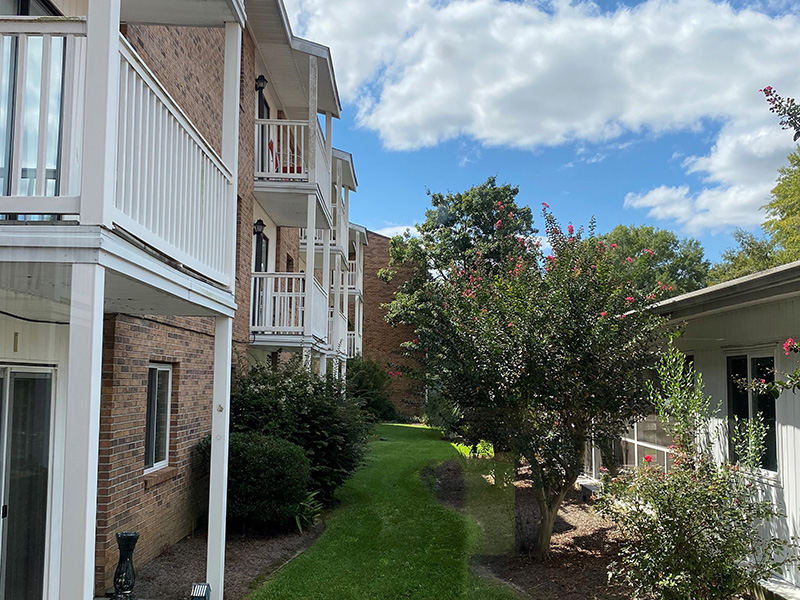 Apartment balconies with a grass path below and trees.