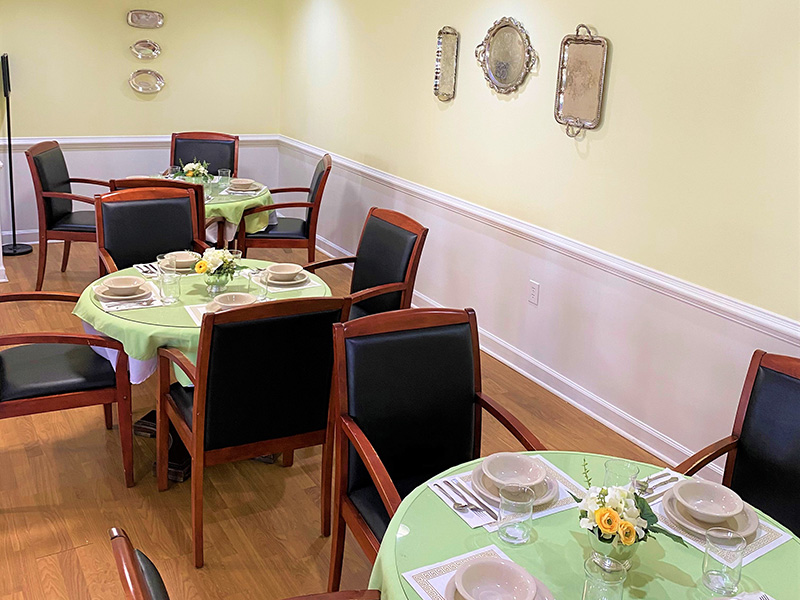A dining room with decorative dishes on the wall. Tables are nicely set with flowers in the middle of the tables.