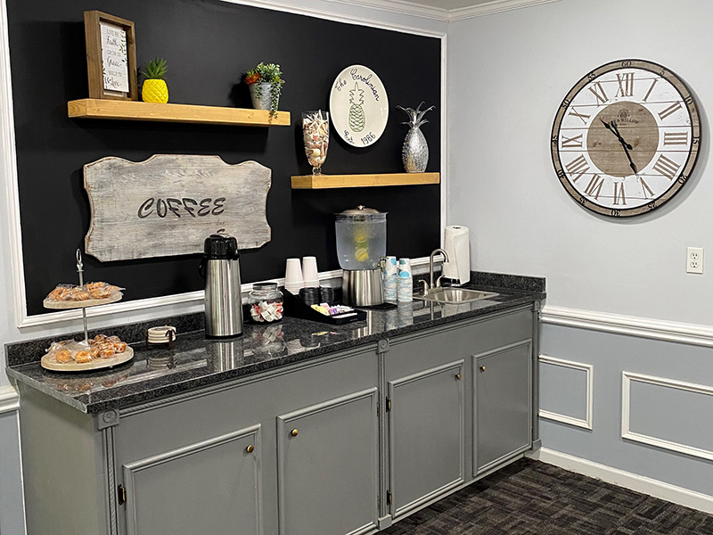 A snack and beverage bar area with open shelves and a large clock on the wall.