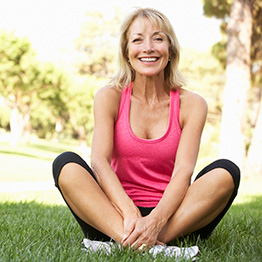 woman dressed in workout gear sitting outside on the grass