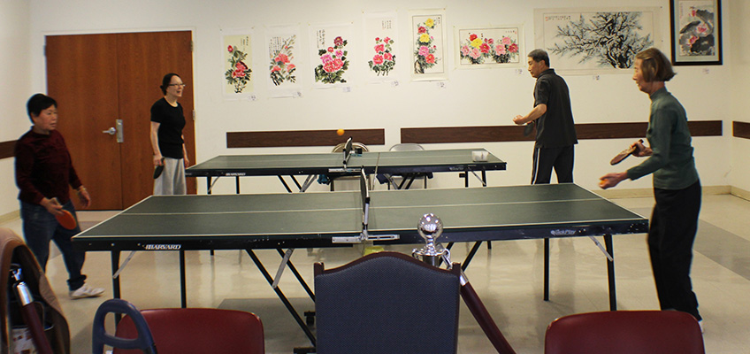 residents playing ping pong in the recreation room