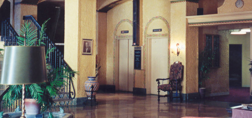 Lobby area of LaFontaine with golden walls, elevators and stairs