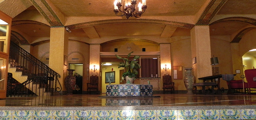 Decorative tiled stairs leading up to the lobby area with a large chandelier and planter next to the front desk and stairs