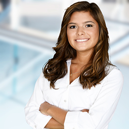 A woman standing in business attire with her arms folded in front of her