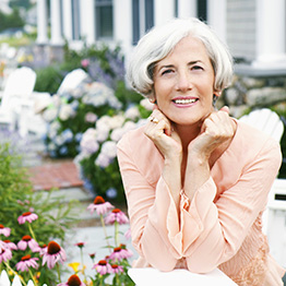 A woman with her elbows resting on a railing with various flowers behind her