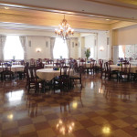 LaFontaine Center Grand Ballroom with a large chandelier and chairs around tables with covers on them on a checkered floor