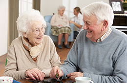 Elderly couple playing dominoes with a woman being assisted in the background by a nurse
