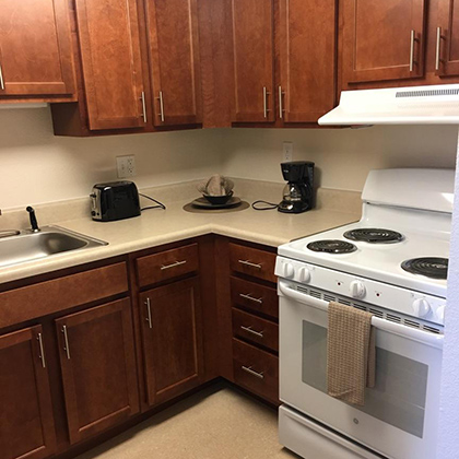 Kitchen with clean stove, wood cabinets with a toaster and coffee maker on the counter