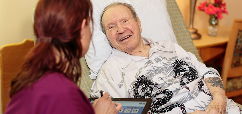 patient with a interesting shirt talking to a nurse using an ipad
