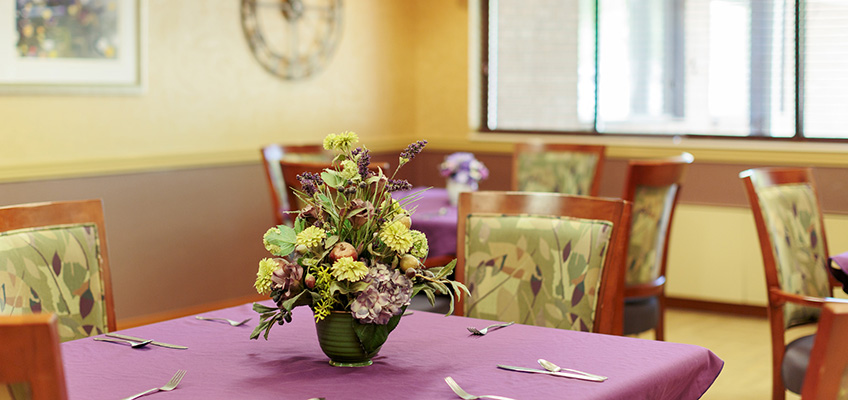 dining area with flowers in the center of the table