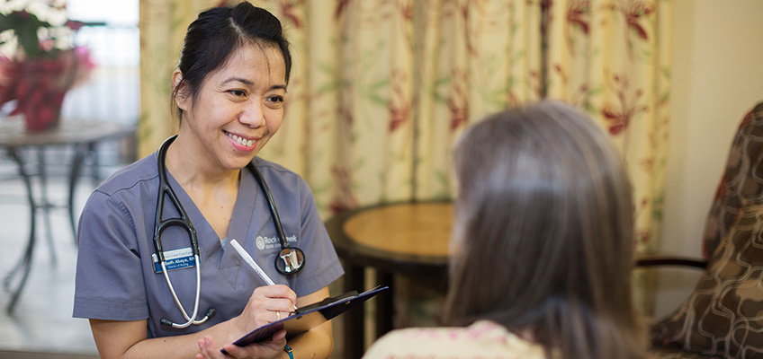 woman doctor talking with resident and writing on a clip board