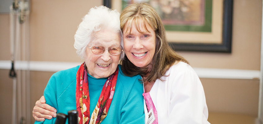 smiling elderly woman and nurse