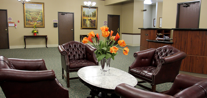 four leather chairs with marble table and flower arrangement