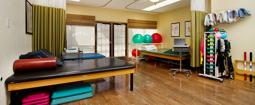 rehabilitation room full of yoga balls and tables