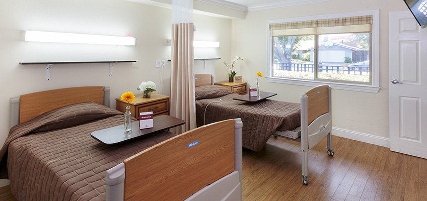 Double occupancy room with nicely made beds, flowers on the food table and clean wood floors.