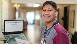 A nurse smiling in front of a resident room with a laptop beside him.