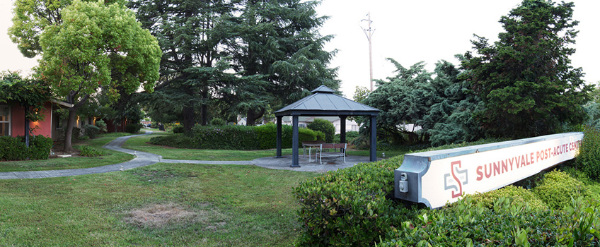 The Sunnyvale sign with a gazebo and seating behind it beside the walking path.