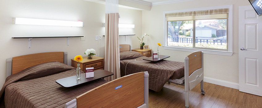 A double occupancy bedroom with a large window for natural lighting and flowers on the nightstand and food table.