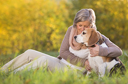 Woman snuggling her Beagle in a meadow