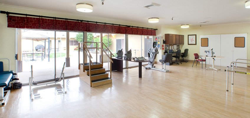 rehabilitation area with a large glass wall and various rehab equipment