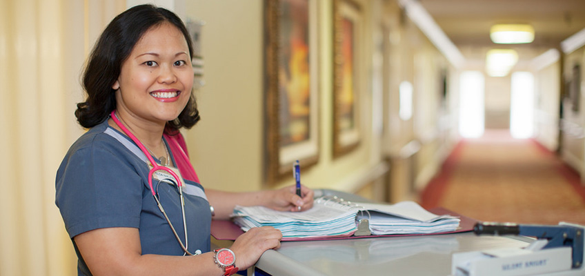 smiling nurse with a stethoscope filling out paperwork