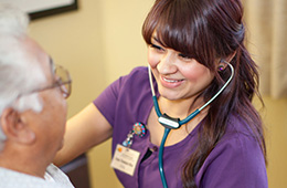 smiling nurse with a stethoscope helping an older man
