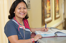 smiling nurse filling out paperwork