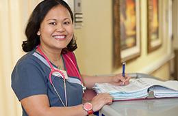 smiling nurse filling out paperwork