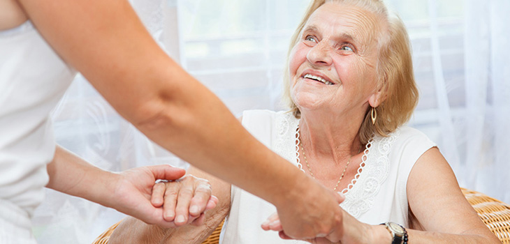 A staff member holding the hands of a resident helping her up