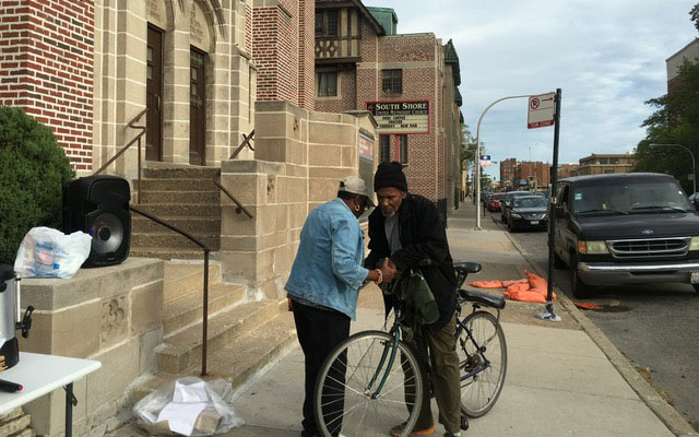 Displaying discipleship in action, a Southshore UMC member prays with a stranger on a bike.