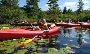 Kids Kayaking on Lake with Lily Pads