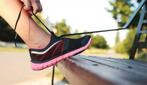 Person Tying Pink Athletic Shoe on Park Bench