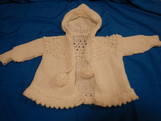 White hooded baby sweater donated by Carol Turkett, member of SAWSs