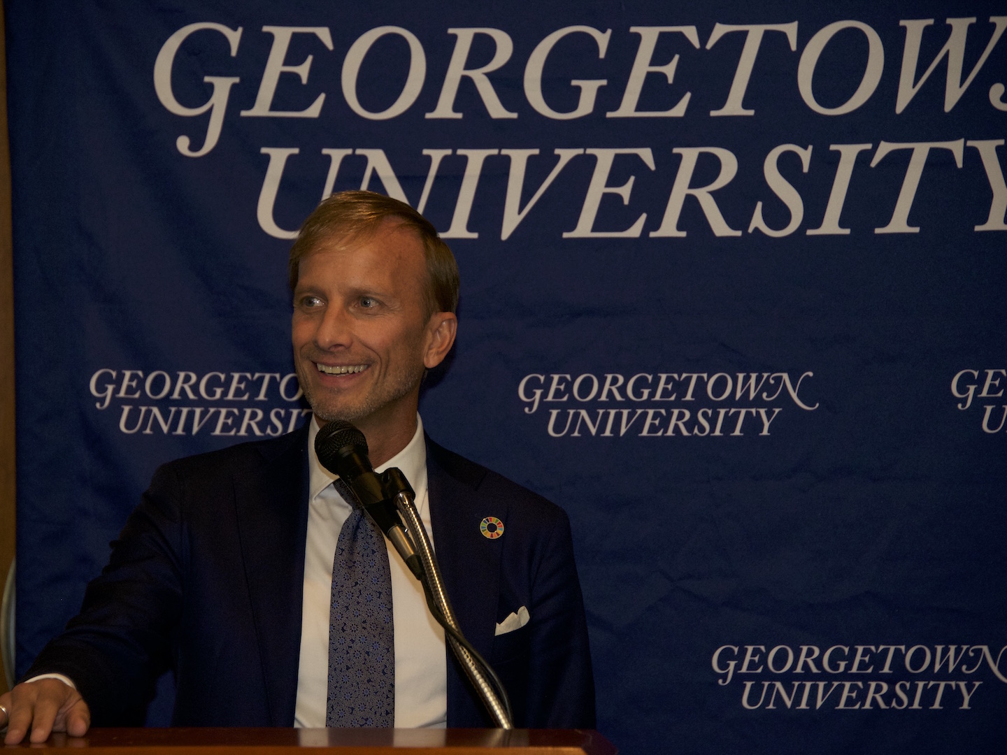 Mark Dybul in front of Georgetown banner